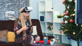 Medium close up of nice girl playing a game with joystick in virtual reality glasses. Medium close up of nice girl playing a game in virtual reality glasses in stock video footage