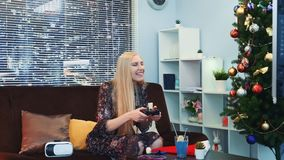 Medium close up of nice girl playing on playstation near the Christmas tree. There are also VR glasses headset on sofa in the room with skyscrapers in the stock video footage