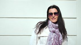 Medium close-up portrait casual smiling spring woman posing at white wall outdoor background. Looking at camera. Charming girl wearing sunglasses scarf playing stock video footage