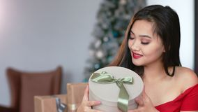 Medium close-up portrait of charming elegant Asian young woman holding gift box and smiling. In background Christmas tree and cozy home interior. Beautiful