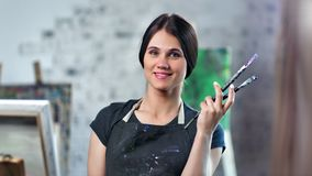 Medium close-up portrait happy female painter posing holding professional art brush. Looking at camera. Smiling creative artist wearing apron soiled by paint stock video footage