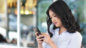 Portrait pensive Asian businesswoman looking screen writing message chatting using smartphone stock video footage