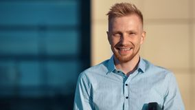 Medium close-up smiling young charming businessman looking at camera standing outdoor. At modern building background. Portrait of happy guy having positive stock video footage