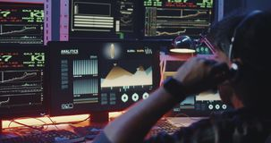 Hacker using computer with multiple monitors. Medium close-up of a young hacker using a computer with multiple monitors stock footage