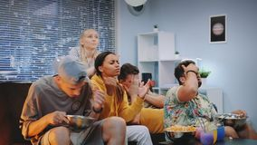Medium close up of young people showing their negative reation to action on TV. The boy throwing down his cap and one girl leaving the room stock video footage
