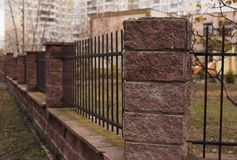 Medium fence with rock columns. Medium fence with brown rock columns Royalty Free Stock Photo