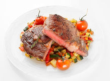 Medium fried steak with vegetables shot on light background Stock Photo