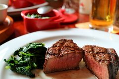 Free Medium Grilled Tenderloin Steak Cut In Half With Sauteed Spinach On White Plate Royalty Free Stock Photo - 99992525