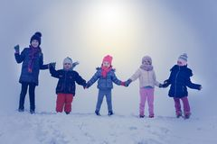 Medium group of children standing in the snow. royalty free stock photo