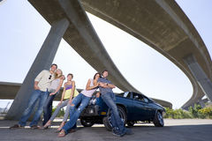 Medium group of friends on bonnet of car beneath overpass, smiling, portrait, low angle view Royalty Free Stock Photo