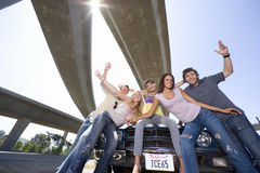 Medium group of friends on bonnet of car beneath overpass, smiling, portrait, low angle view (sun flare) Royalty Free Stock Photos
