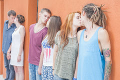 Medium group ofpeople kissing and standing near red wall background Royalty Free Stock Photo