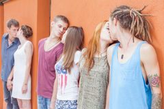 Medium group of people kissing and standing near red wall background Royalty Free Stock Images