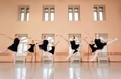 Medium group of teenage girls practicing classical ballet in a large dancing studio royalty free stock images