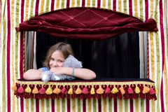 Little girl squeezing stuffed animal puppet in small puppet theater stock photography