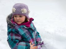 Forlorn-looking little girl in snowsuit standing in snow looking back royalty free stock photos
