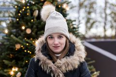 Young girl in fur trimmed black winter coat with lighted Christmas tree in soft focus background. Medium horizontal shot of pretty smiling young woman in fur Stock Photos