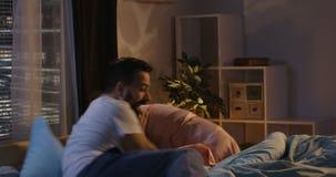 Pillow fight in bedroom. Medium long shot of couple having pillow fight in bedroom stock footage