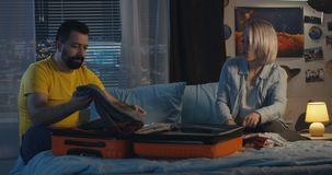 Couple packing into a suitcase. Medium long shot of couple packing a suitcase in children`s room stock footage