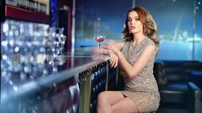 Medium long shot fashionable young woman wearing shiny dress sitting on bar with glass of wine. Charming female having good evening at luxury interior stock video