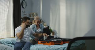 Couple packing in bedroom. Medium long shot of man helping woman packing in bedroom stock footage