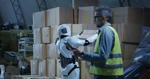 Man watching robot working in a warehouse. Medium long shot of a man using a tablet while watching a robot working in a warehouse stock video