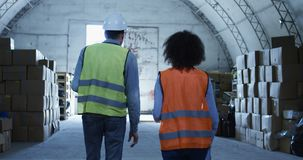 Manager giving out instruction in a warehouse. Medium long shot of manager giving out instruction in a warehouse stock video footage