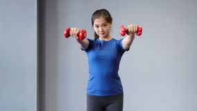 Medium long shot smiling Asian sports woman doing exercise lifting dumbbells in front of herself stock video footage