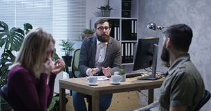 Troubled young couple in the office of a psychologist stock video footage