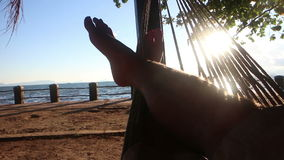 Medium POV perspective person crosses legs while swinging gently in a hammock by the sea stock video footage