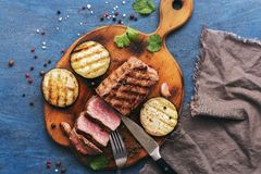 Medium rare beef steak is cut on a cutting board. View from above.  stock photo
