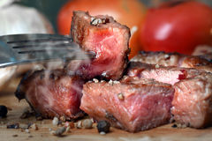 Medium rare beef steak grill in charcoal flamimg Royalty Free Stock Photography