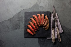 Medium rare beef steak on slate board, vintage cutlery Royalty Free Stock Photography