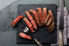 Medium rare beef steak on slate board, vintage cutlery Stock Photo