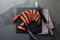 Medium rare beef steak on slate board, vintage cutlery Royalty Free Stock Photos