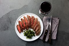 Medium rare beef steak on white plate, glass of red wine. Slate background royalty free stock photos