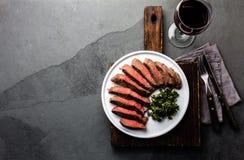 Medium rare beef steak on white plate, glass of red wine. Slate background Stock Photo