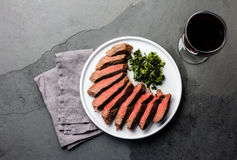 Medium rare beef steak on white plate, glass of red wine Stock Images