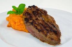 Medium Rare Beefsteak with Sweet Potato. Beefsteak with sweet potato on white dish isolated on white background Royalty Free Stock Image