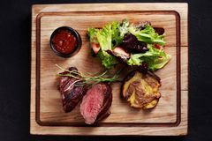 Medium rare fillet steak mignon, grilled meat. Juicy medium rare fillet steak mignon served with vegetable salad and potatoes on board, traditional american stock photos