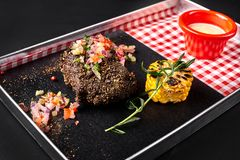 Medium rare grilled Beef steak Ribeye with corn, rosemary, onion and white sauce on a metal tray on a black background. Concept restaurant menu. Still life royalty free stock photography