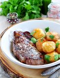 Medium rare grilled Beef steak with roasted potato Royalty Free Stock Images