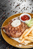 Medium rare grilled beef steak on on wooden black background on  brown plate. Steak on a plate with different fillings medium medium sauce with butter sauce, on Stock Images