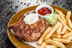 Medium rare grilled beef steak on on wooden black background on  brown plate. Steak on a plate with different fillings medium medium sauce with butter sauce, on Stock Photos