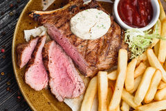 Medium rare grilled beef steak on on wooden black background on  brown plate. Steak on a plate with different fillings medium medium sauce with butter sauce, on Royalty Free Stock Photography
