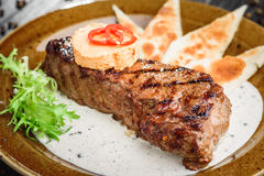 Medium rare grilled beef steak on on wooden black background on  brown plate. Steak on a plate with different fillings medium medium sauce with butter sauce, on Royalty Free Stock Photo