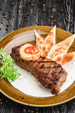 Medium rare grilled beef steak on on wooden black background on  brown plate. Steak on a plate with different fillings medium medium sauce with butter sauce, on Royalty Free Stock Photos