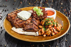 Medium rare grilled beef steak on on wooden black background on  brown plate. Steak on a plate with different fillings medium medium sauce with butter sauce, on Stock Photography