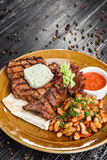 Medium rare grilled beef steak on on wooden black background on  brown plate Stock Image