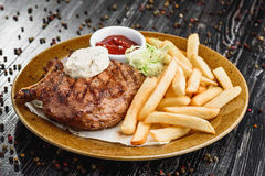 Medium rare grilled beef steak on on wooden black background on  brown plate Royalty Free Stock Photo
